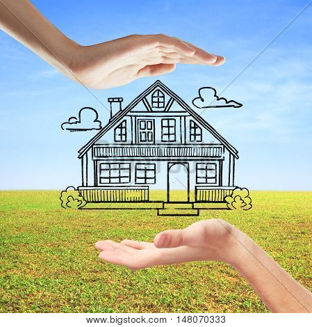 Hands holding creative house sketch on beautiful landscape background. Mortgage concept
