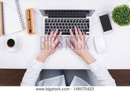 Top view of businesswoman's hands typing on laptop keypad placed on white office desktop with blank smartphone coffee cup decorative plant and supplies. Mock up