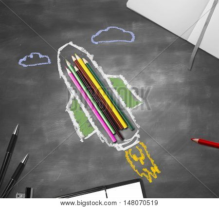 Abstract rocket ship sketch around colorful pencils on chalkboard surface with other supplies. Education concept