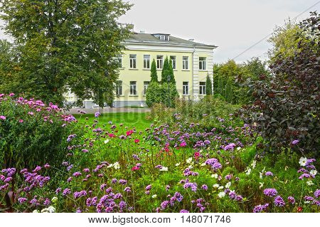 beautiful summer garden landscape with flowers trees and building on the background