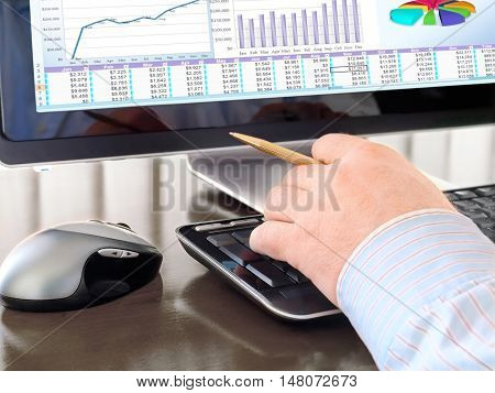 Male hand with Pen on the Keyboard in front of Computer Screen with Charts