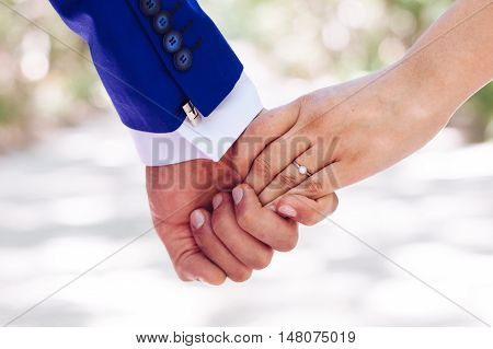Bride and groom holding hands close up. Wedding ring with a diamond