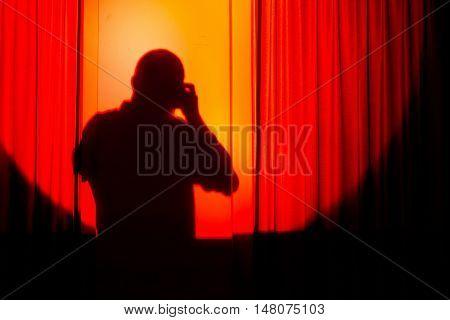 silhouette of photographer on orange courtain taking photos