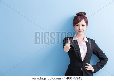 business woman is smile to you and thumbs up isolated on blue background asian