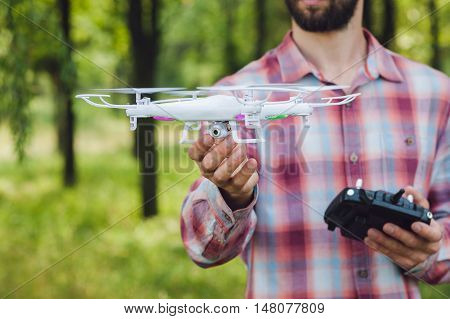 Unrecognizable man running drone with camera in forest. Review of new unmanned aerial quadrocopter outdoor. Modern tool for overhead photo and video