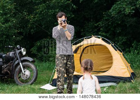 Father taking photo of his daughter in forest. Summer week-end outdoors, family trip