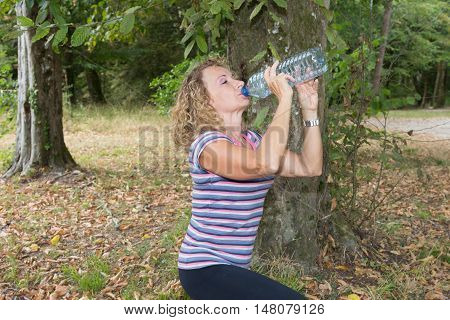 Portrait Of A Blond Woman Drinking Water At Summer Green Park.