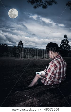 Happy asian child drawing on wooden log at park with bright full moon. Conceptual of outdoors learning or education. Low key and high contrast style. The moon were NOT furnished by NASA.