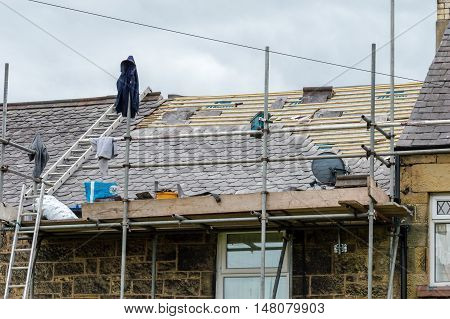 WREXHAM WALES UNITED KINGDOM - AUGUST 10 2016: Restoration of decorative slate roof on a residential terraced house in North Wales.
