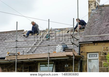 WREXHAM WALES UNITED KINGDOM - AUGUST 11 2016: Restoration of decorative slate roof on a residential terraced house in North Wales. With two skilled roofers.