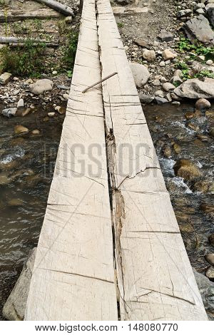 Homemade bridge over a mountain stream consisting of two logs fastened metal bracket
