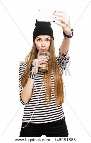 Cute millennial blonde teenage girl, drinking coffee, taking a selfie on smart phone. Modern young woman in black and white outfit and striped shirt photographing herself. Isolated on white background.