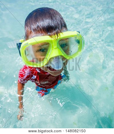 Clouse up photo of happy snorkeling boy in yellow mask