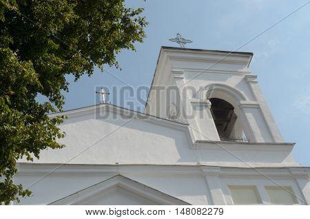 Faith Catholic Church against the blue sky and tree.