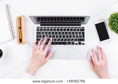 Top view of girl's hands typing on laptop keypad placed on white office desktop with blank smartphone coffee cup decorative plant and supplies. Mock up