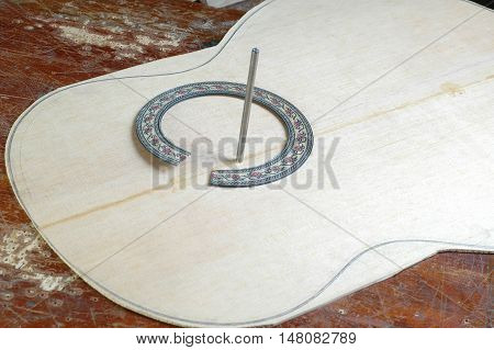 Harvesting of the top deck and rosette classical guitar before a hole