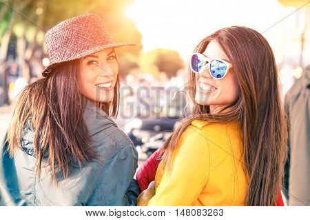 Young women walking on the street turning back and smiling - Cheerful girlfriends carefree attitude looking at camera outdoors with day light and car background - Concept of friendship and leisure poster