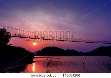 Landscape and people in silhouette on bridge with sunset at lake from Kaeng Krachan National Park Thailand