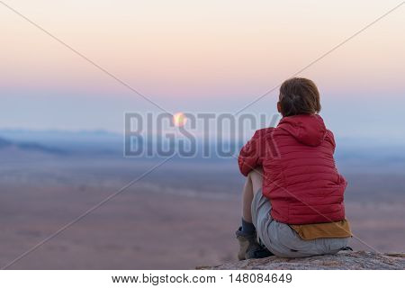 Relaxed Tourist Sitting On Rocks And Looking At The Sunset In The Namib Desert, Best Travel Destinat