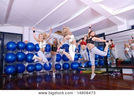 happy girls jumping in fitness cloub