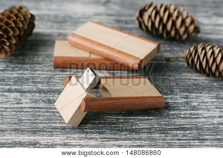 Creative wooden usb sticks on dark background. Wooden USB flash drives for photographer on white and black table. With fir cone