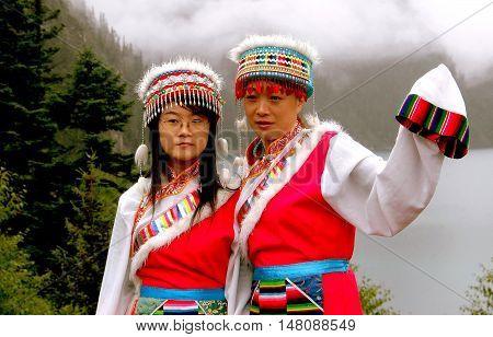 Jiu Zhai Gou / Sichuan China - Augst 22 2006: Two Chinese women wearing traditional Chiang clothing with ornate hats