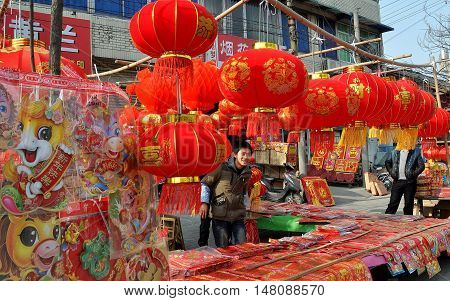 Jun Le China - January 25 2014: Young boy selling red lanterns and other decorations for the Chinese Lunar New Year holiday