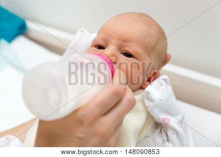 mother feeds their newborn infant baby with bottle