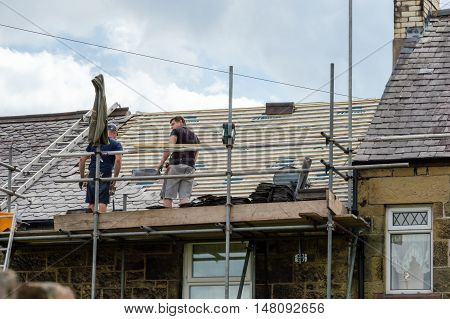 WREXHAM WALES UNITED KINGDOM - AUGUST 05 2016: Restoration of decorative slate roof on a residential terraced house in North Wales. With two workmen.