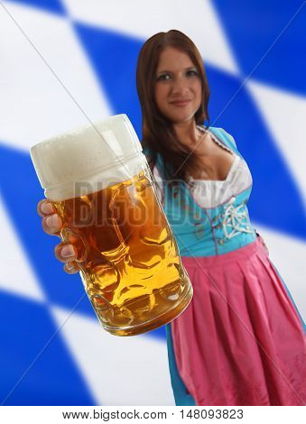 Bavarian Waitress holding Oktoberfest Beer with a bavarian flag in the background