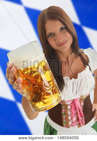 Bavarian Woman in traditional dirndl clothing holding Oktoberfest Beer with a bavarian flag in the background
