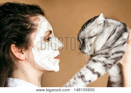 Funny woman cosmetic mask close-up. On the girl's face rejuvenating mask. striped cat