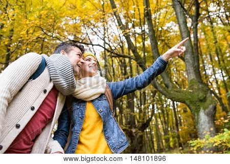 Beautiful couple on a walk in colorful autumn forest. Woman pointing at something with her finger.
