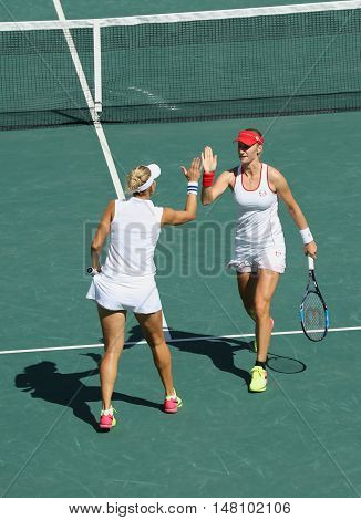 RIO DE JANEIRO, BRAZIL - AUGUST 14, 2016: Elena Vesnina (L) and  Ekaterina Makarova of Russia in action during women's doubles final  of the Rio 2016 Olympic Games at the Olympic Tennis Centre