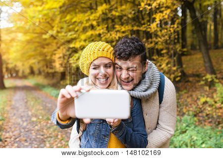 Beautiful young couple on a walk in colorful autumn forest., hugging, taking selfie with smart phone, winking.