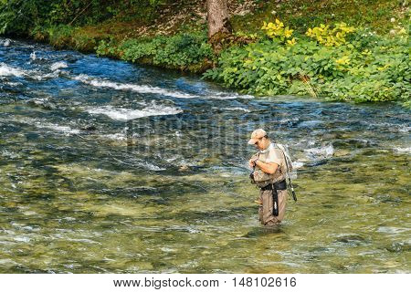 RIBCEV LAZ SLOVENIA - AUGUST 22 2016: Unidentifiable man fishing at Jezernica second shortest river in Slovenia flowing from Lake Bohinj for 100 meters to join Mostnica and form Sava Bohinjka.