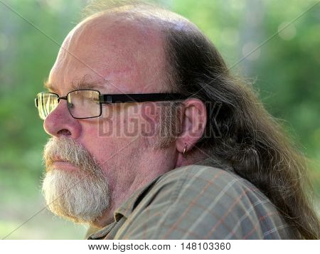 Older senior aged man with long hair and a gold earing: Profile