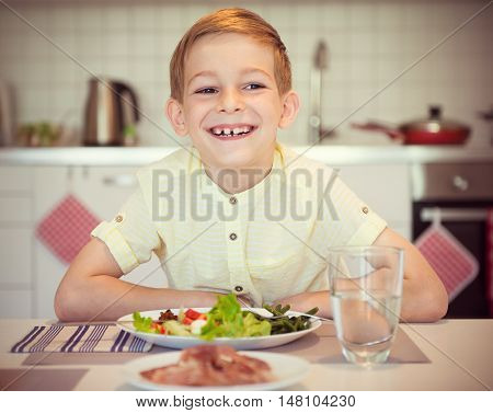 Young Diligent Happy Boy  At A Table Eating Healthy Meal With Cutlery