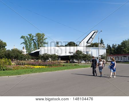 Moscow - 24 August 2015: Happy people and tourists walk in a beautiful park near the Exhibition of Economic Achievements of the Soviet Buran reusable space rocket August 24 2015 Moscow Russia