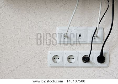 electrical plugs in wall outlet on white wall