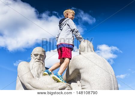 Oslo, Norway - August 11, 2016: Smiling boy over sculpture in Vigeland Park, the world's largest sculpture park made by a single artist, and one of Norway's most popular tourist attractions.