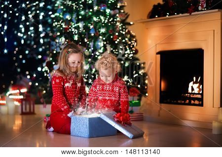 Family on Christmas eve at fireplace. Kids opening Xmas presents. Children under Christmas tree with gift boxes. Decorated living room with traditional fire place. Cozy warm winter evening at home.