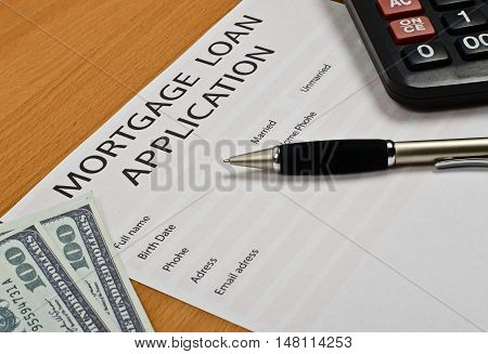 the application form for a mortgage loan is on the table. next pen calculator money