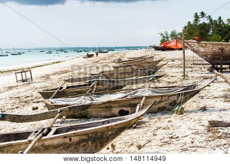 many old wooden fishing boats on african seashore with ocean on the background
