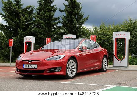 PAIMIO, FINLAND - JULY 31, 2016: Tesla Model S luxury sedan with new design on the vehicle exterior is being charged at Tesla Supercharger Station in South of Finland.