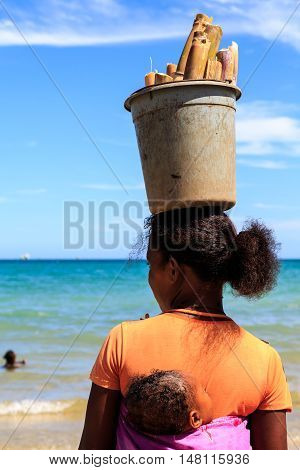 Woman Carrying A Baby And A Heavy Bucket With Bamboo On Her Head