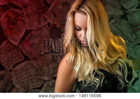 a sexy young woman with loose long blond hair in a black bodysuit in the unusual dark background of newspapers. Her eyes are closed