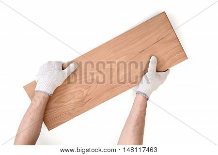 Close up view of a man's hands in white cotton gloves holding wooden plank isolated on white background. Building and construction. Handyman. DIY.