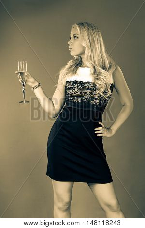 a young woman with loose long blond hair in a black and white dress is holding a glass of wine in her hand in the background of sunbeams. Monochrome