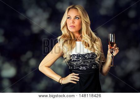 a young woman with loose long blond hair in a black and white dress is holding a glass of wine in her hand in the dark background